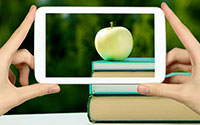 image of a cellphone taking a picture of an apple and a stack of books